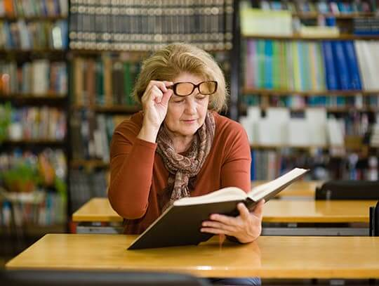Woman having trouble reading in library